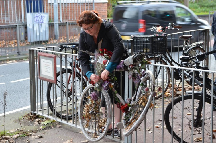 Flowers being placed on Jaye Bloomfield's ghost bike (close-up)